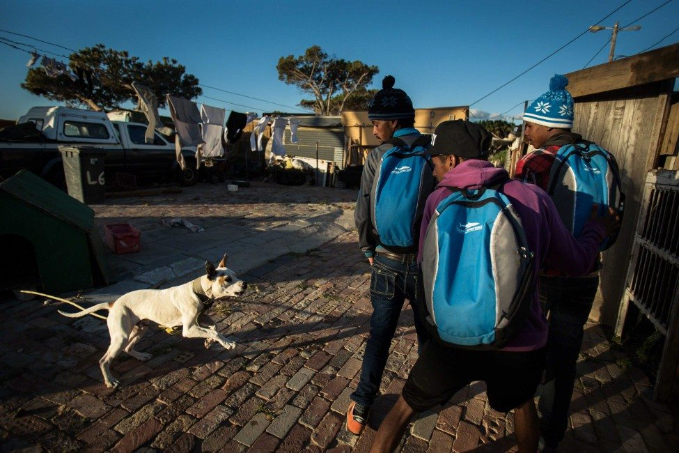 Many of the Shark Spotters live in crowded and impoverished townships outside Cape Town. Funded by the local municipality, local businesses and the Save Our Seas Foundation, the programme provides much-needed jobs and income to under-served communities. Its members wear their branded backpacks and shirts with pride in the communities.