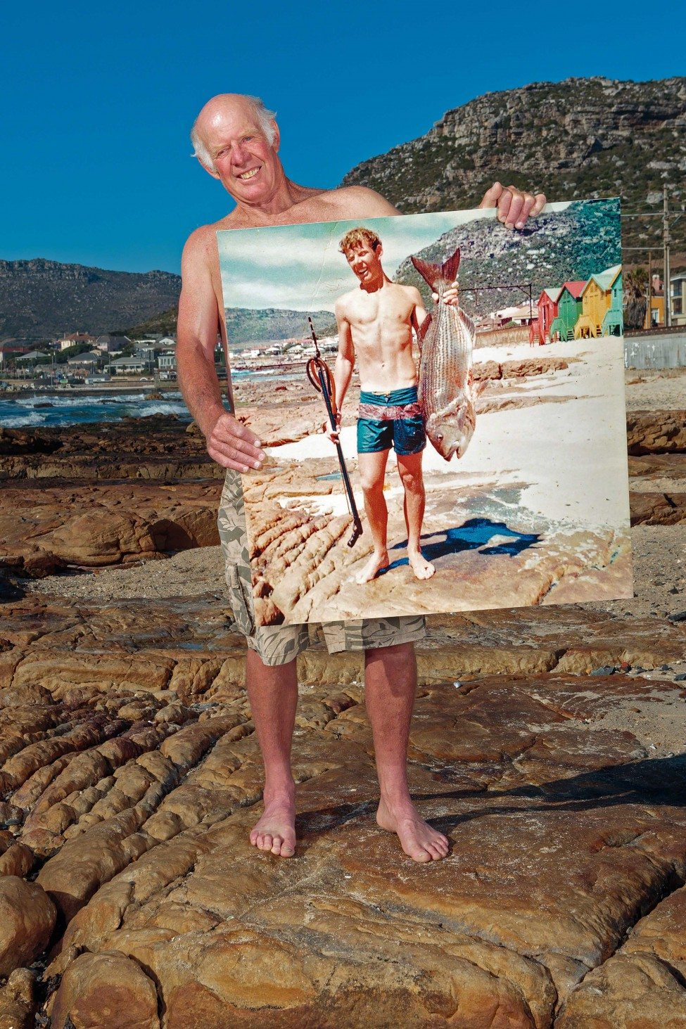 In December 1968, Geoff Fridjhon posed for a photo holding a large white musselcracker Sparodon durbanensis he had caught while spearfishing off Dalebrook beach. A fish of this size would have been close to 30 years old. Forty-six years later Fridgeon stands in the exact same spot holding an enlargement of the photo. Today the species has all but disappeared from False Bay. A white musselcracker can take more than five years to reach sexual maturity, which makes the species highly susceptible to overfishing.